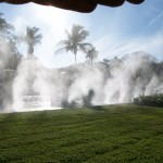The sun lights up the mist in this photo of a Misting Direct brand system installed by Outdoor Cooling Systems.