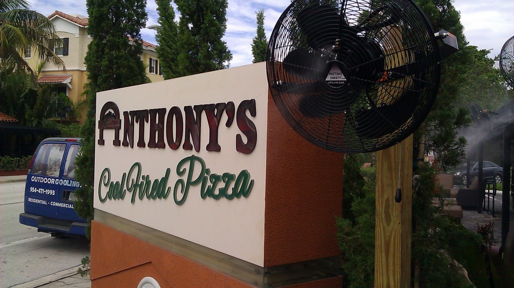 One Misting Fan is show with the Anthony's Coal Fired Pizza Sign In Delray Beach ,Florida.